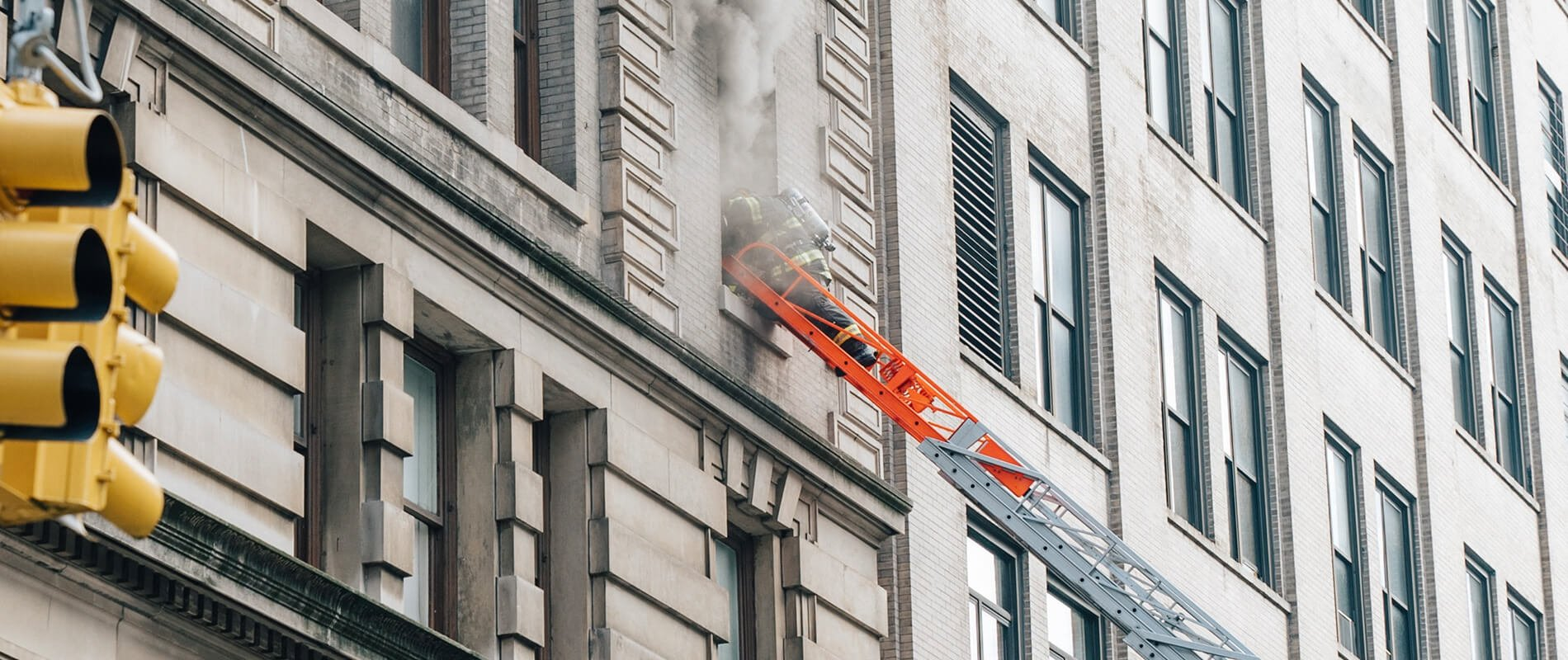 firefighter on ladder on building - self closing door hinge fire security systems installation nh